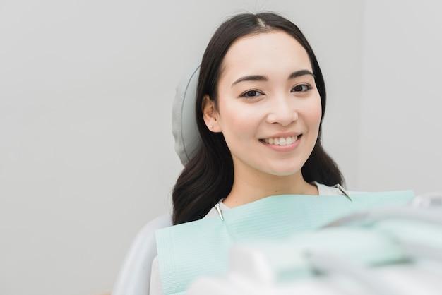 Uśmiechnięta kobieta przy dentystą