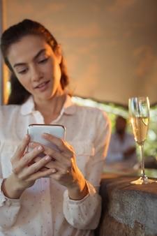Uśmiechnięta kobieta przy lampce szampana przy użyciu telefonu komórkowego
