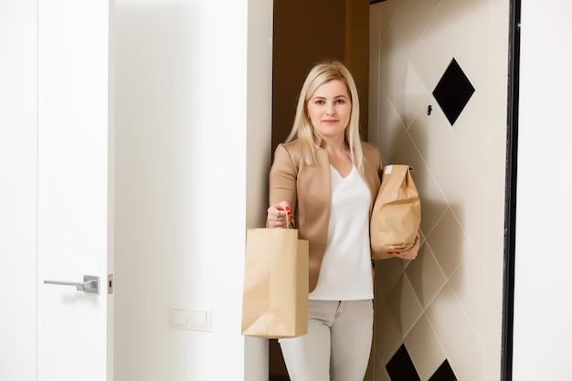 Uśmiechnięta kobieta przyniosła zamówione jedzenie z dostawy w domu