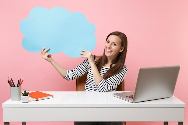 Uśmiechnięta kobieta przytrzymaj niebieski pusty pusty powiedz chmura dymek siedzieć przy białym biurku z laptopem pc na białym tle na pastelowym różowym tle. koncepcja kariery biznesowej osiągnięcia. skopiuj miejsce na reklamę.