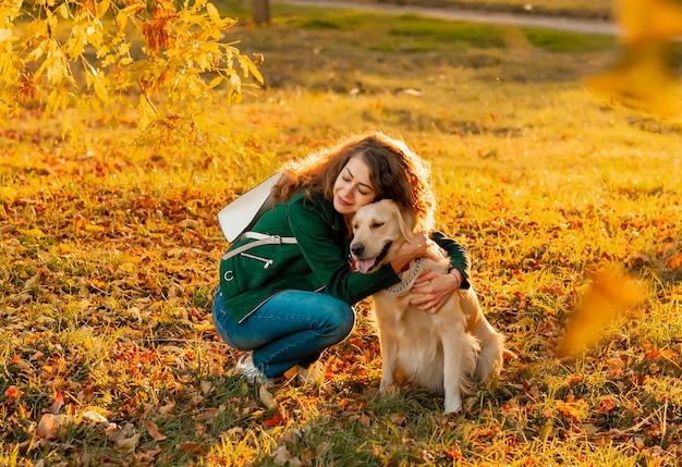 Uśmiechnięta kobieta przytulanie psa golden retriever w pobliżu twarzy