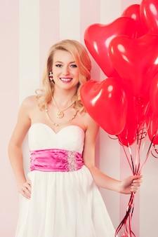 Uśmiechnięta kobieta retro z czerwonymi balonami w kształcie serca