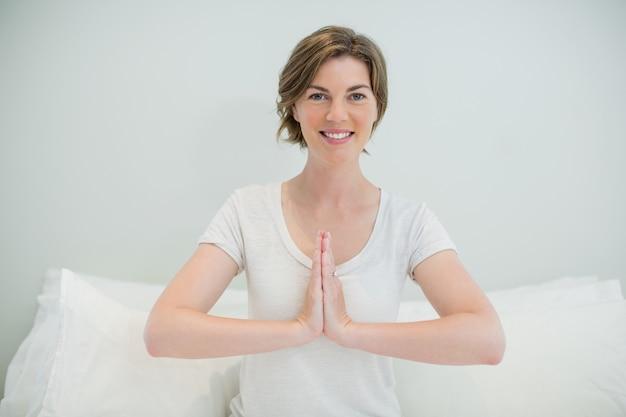 Uśmiechnięta kobieta robi medytację na łóżku w sypialni w domu
