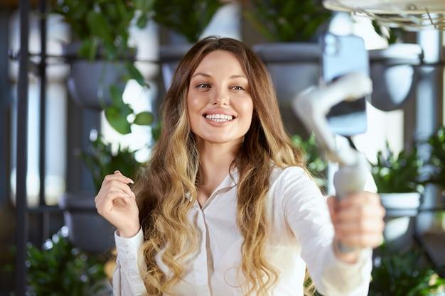 Uśmiechnięta kobieta robi wideo lub selfie w kawiarni