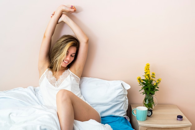 Uśmiechnięta kobieta rozciąganie w łóżku