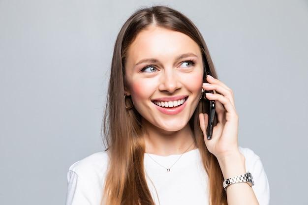 Uśmiechnięta kobieta rozmawia przez inteligentny telefon na białym tle