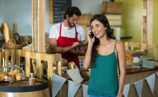 Uśmiechnięta kobieta rozmawia przez telefon komórkowy przy ladzie