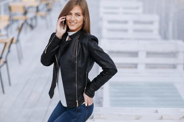 Uśmiechnięta kobieta rozmawia przez telefon komórkowy z jednej strony w kieszeni