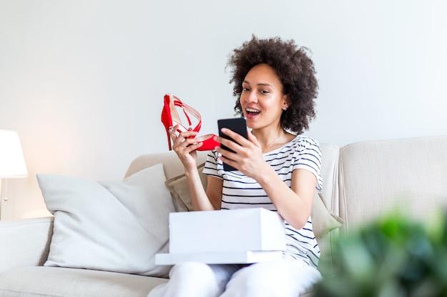 Uśmiechnięta kobieta rozpakowuje paczkę pocztową i robi selfie ze swoimi nowymi zakupami za pomocą smartfona.