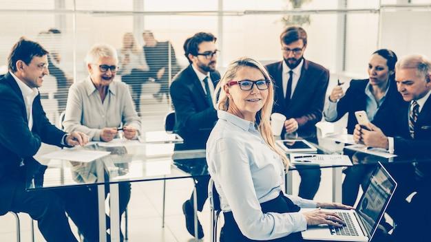 Uśmiechnięta kobieta rozpoczyna spotkanie robocze z zespołem biznesowym. pomysł na biznes.