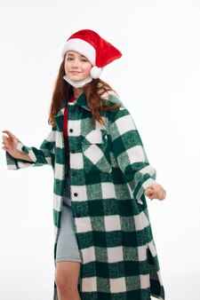 Uśmiechnięta kobieta santa hat płaszcz w kratę pozowanie na jasnym tle