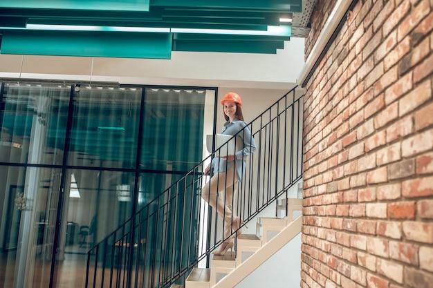 Uśmiechnięta kobieta schodząca po schodach z laptopem