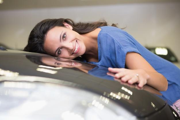 Uśmiechnięta kobieta ściska czarnego samochód
