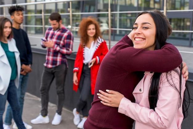 Uśmiechnięta kobieta ściska jej przyjaciela patrzeje kamerę