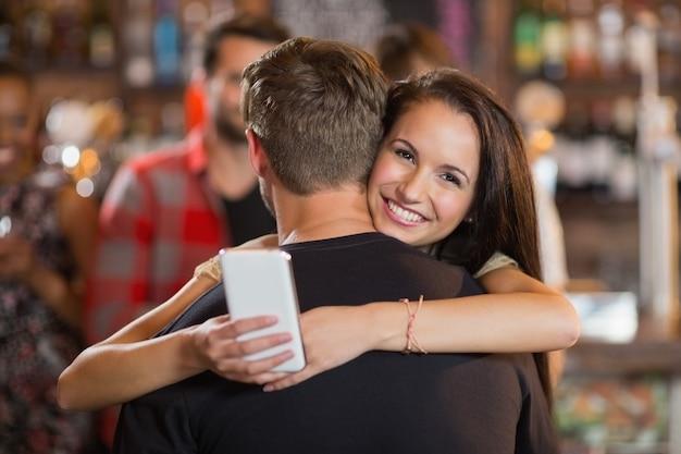 Uśmiechnięta kobieta ściska swojego chłopaka