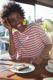 Uśmiechnięta kobieta siedząca w kawiarni