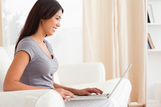 Uśmiechnięta kobieta siedzi crossleged na kanapie pracy z notebooka