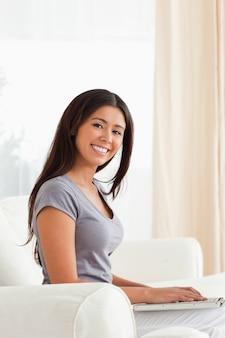 Uśmiechnięta kobieta siedzi na kanapie patrząc w kamerę