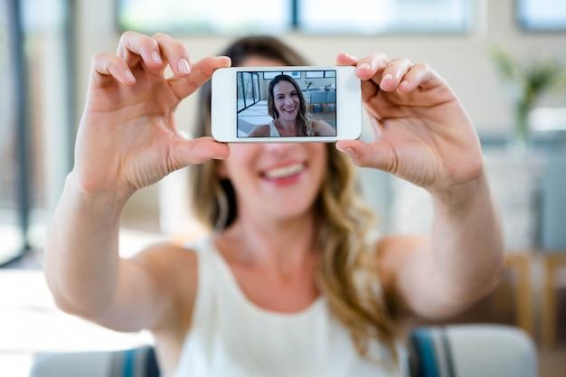 Uśmiechnięta kobieta siedzi na kanapie przy selfie na jej telefon komórkowy
