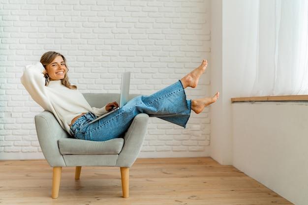 Uśmiechnięta kobieta siedzi na kanapie w domu, pracując na laptopie