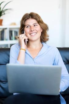 Uśmiechnięta kobieta siedzi na kanapie w domu za pomocą laptopa