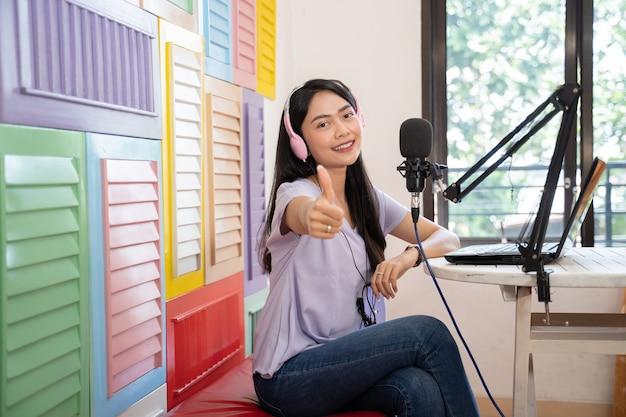 Uśmiechnięta kobieta siedzi na kanapie w słuchawkach, patrząc na kamerę z kciukami do góry