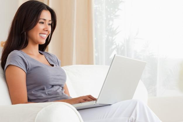 Uśmiechnięta kobieta siedzi na kanapie z notebooka
