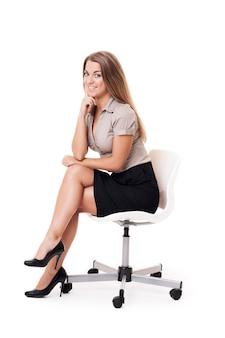 Uśmiechnięta kobieta siedzi na krześle biurowym