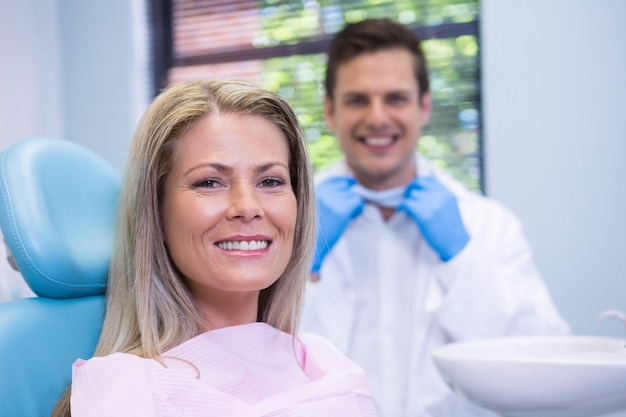 Uśmiechnięta kobieta siedzi na krześle przed dentystą w przychodni