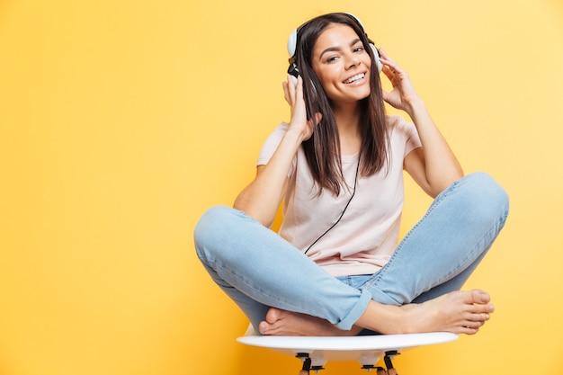 Uśmiechnięta kobieta siedzi na krześle z zestawem słuchawkowym nad żółtą ścianą