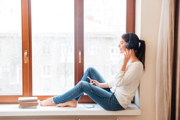 Uśmiechnięta kobieta siedzi na parapecie i słucha muzyki w słuchawkach w domu