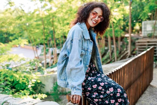 Uśmiechnięta kobieta siedzi na płocie w słoneczny letni park z fryzurą