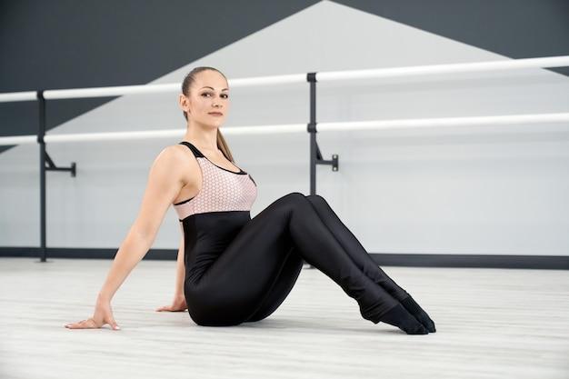 Uśmiechnięta kobieta siedzi na podłodze w studiu tańca