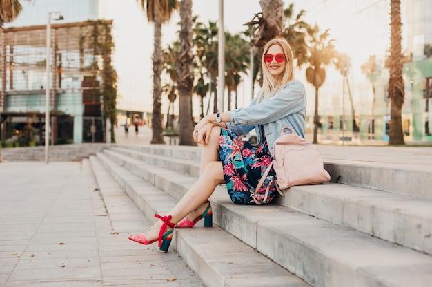 Uśmiechnięta kobieta siedzi na schodach na ulicy miasta w stylowej drukowanej spódnicy i dżinsowej kurtce oversize ze skórzanym plecakiem na sobie różowe okulary przeciwsłoneczne