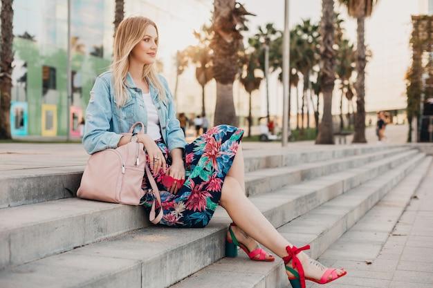 Uśmiechnięta kobieta siedzi na schodach na ulicy miasta w stylowej drukowanej spódnicy i dżinsowej kurtce oversize ze skórzanym plecakiem