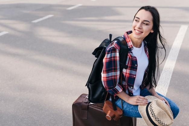 Uśmiechnięta kobieta siedzi na torbie bagażowej z aparatu i plecaka w plenerze