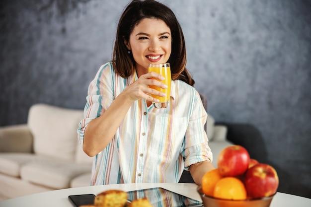 Uśmiechnięta kobieta siedzi przy stole w godzinach porannych i zdrowe śniadanie.