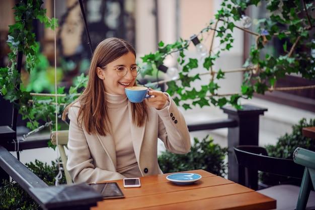 Uśmiechnięta kobieta siedzi w kawiarni na świeżym powietrzu i popijając kawę
