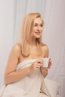 Uśmiechnięta kobieta siedzi w łóżku z filiżanką mleka, odwracając