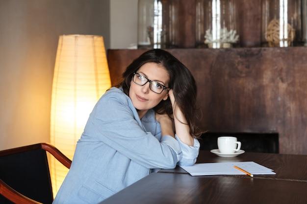 Uśmiechnięta kobieta siedzi w pomieszczeniu blisko filiżanki kawy