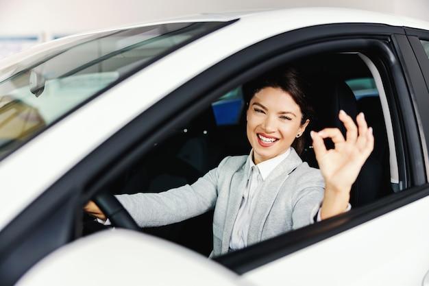 Uśmiechnięta kobieta siedzi w samochodzie, który chce kupić i siać znak porządku.