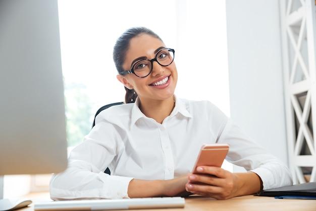 Uśmiechnięta kobieta siedzi w swoim miejscu pracy w biurze i trzyma telefon