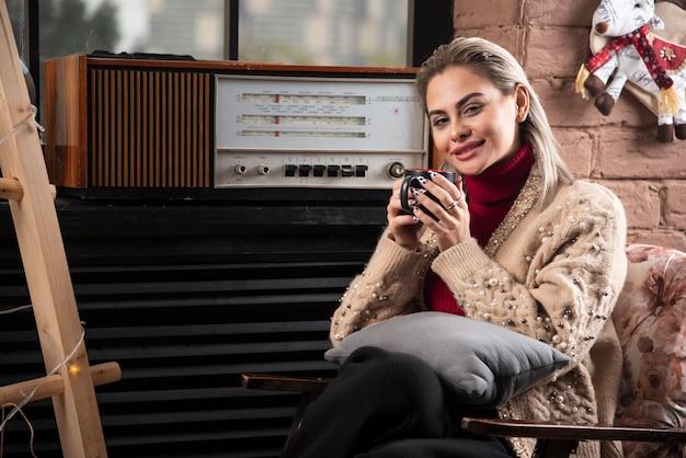 Uśmiechnięta kobieta siedzi z książką i pije kawę