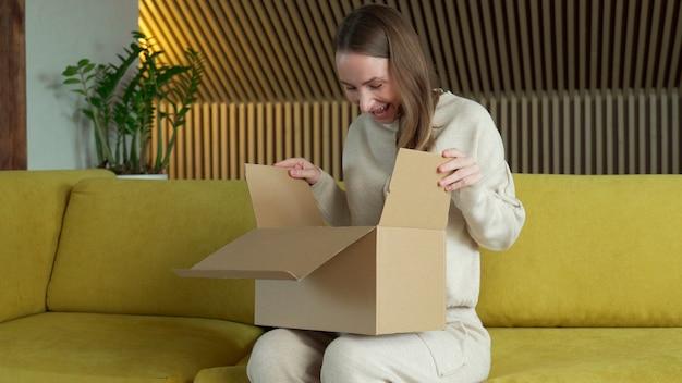 Uśmiechnięta kobieta siedzieć na kanapie w domu otwórz opakowanie kartonowe dostawy zakupów online