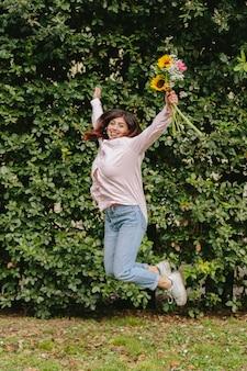 Uśmiechnięta kobieta skacze blisko zielonego krzaka z wiązką kwiaty