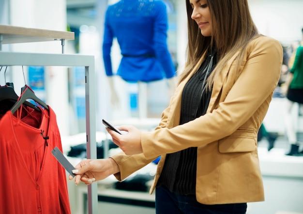 Uśmiechnięta kobieta skanowania kodu qr na inteligentny telefon