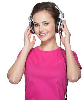 Uśmiechnięta kobieta słucha muzyki na białym tle z hełmofonami