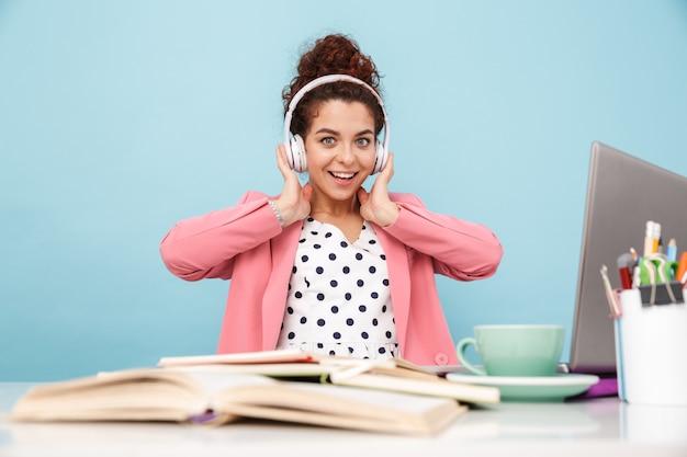 Uśmiechnięta kobieta słuchająca muzyki w słuchawkach podczas pracy przy biurku odizolowanym nad niebieską ścianą
