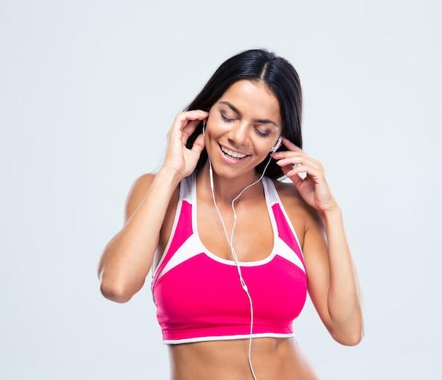 Uśmiechnięta kobieta słuchania muzyki w słuchawkach