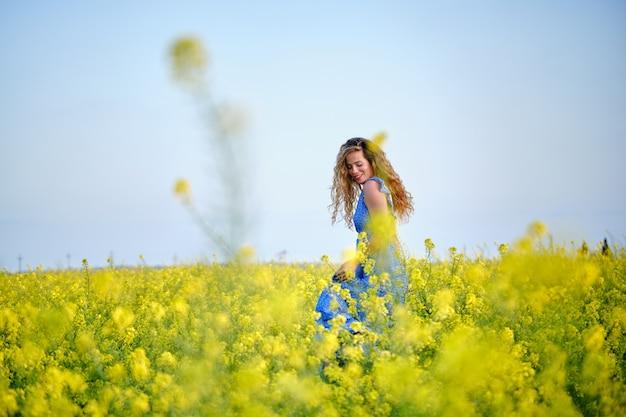Uśmiechnięta kobieta spacerująca po kwitnącym polu kwitnienia